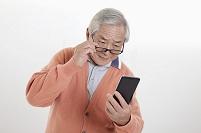 スマートフォンを操作するために眼鏡をずらすシニア男性