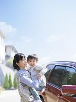 車の前で息子を抱く母親