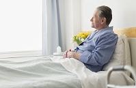 病院のベッドに座るシニア外国人男性