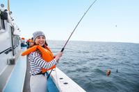 船で海釣りする20代日本人女性