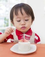 ケーキのろうそくに息を吹く日本人の男の子