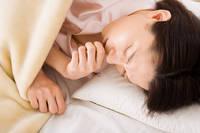 布団の中で咳き込む女性