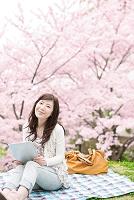 桜とタブレットを持つ日本人女性