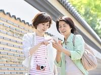 スマートフォンを見る母と娘