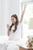 ベッドで体温計を見るパジャマの日本人女性
