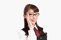 眼鏡に手を添える会社の制服を着た女性