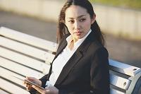 ベンチに座りタブレットを見る女性
