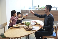 食事をする父親と幼い女の子きょうだい