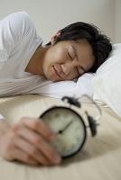 目覚まし時計を持って寝ている日本人男性