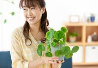 植物を持つ笑顔の日本人女性