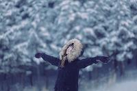 雪が積もった森で手を広げて立つ女性