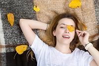 黄葉の葉で目を隠す女性