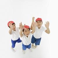 体操着を着て手を上げる日本人の男の子