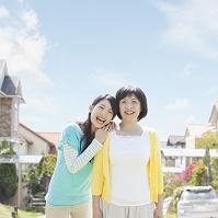 住宅街で寄り添う日本人の母と娘