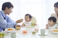 出勤前に朝食をとる共働き夫婦と双子の赤ちゃん