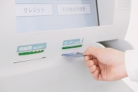 ATMでカードを入れる男性の手