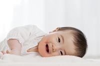 リビングで横になって笑う日本人の赤ちゃん