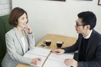 カフェでミーティングをするスーツ姿の日本人男女