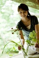 縁側で花を活ける日本人女性