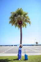 椰子の木にもたれる海のリゾートへ旅する女性