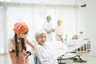介護ベッドと車椅子の介護老人と介護士