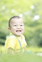 公園の芝生に座る男の赤ちゃん