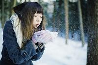 雪に息を吹きかけて飛ばす日本人女性