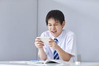 スマートフォンを見る男子中学生