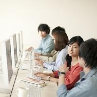 パソコンの画面を見ながら話をする大学生