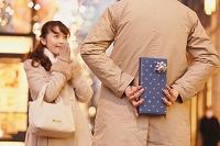 女性にクリスマスプレゼントを渡す男性