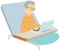 介護ベッド上でパソコンを操作する老人日本人男性
