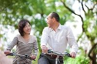 自転車に乗る笑顔の中高年夫婦