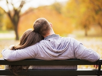 ベンチに寄り添って座る外国人カップル