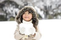 雪山でハートの雪玉を持つ女の子