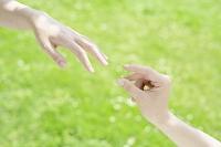 指輪をさしだすカップルの手元