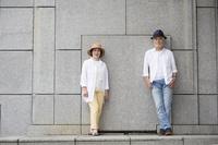 壁の前に立つ日本人シニア夫婦