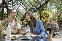 レストランのテラス席で食事を楽しむ外国人カップル