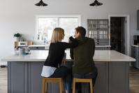 キッチンに並んで座る夫婦