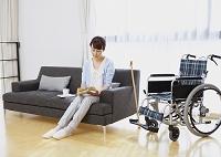 ソファに座って本を読むシニアの女性と車椅子