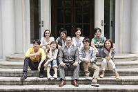 教授を囲み座って微笑む8人の男女大学生