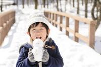 雪山で雪ダルマを持って遊ぶ子供
