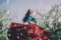 春の風に舞う花びらと踊る女性