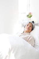 ベッドに横たわるシニア日本人女性患者