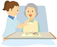 介護ベッドで食事をする老人女性と介護士