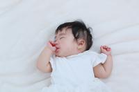 手をしゃぶる寝顔の日本人の赤ちゃん