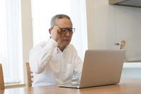 ノートパソコンを使うシニアの日本人男性