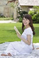 芝生で読書をする若い女性