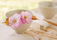 白い器に飾ったピンクの八重桜と木の箸