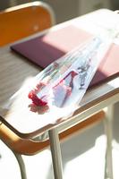 机の上の卒業証書と花