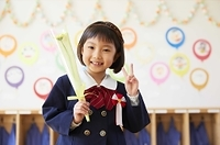 ピースサインをする笑顔の幼稚園児の女の子